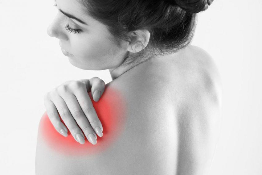 młoda kobieta trzyma sie za bolący zaczerwieniony bark