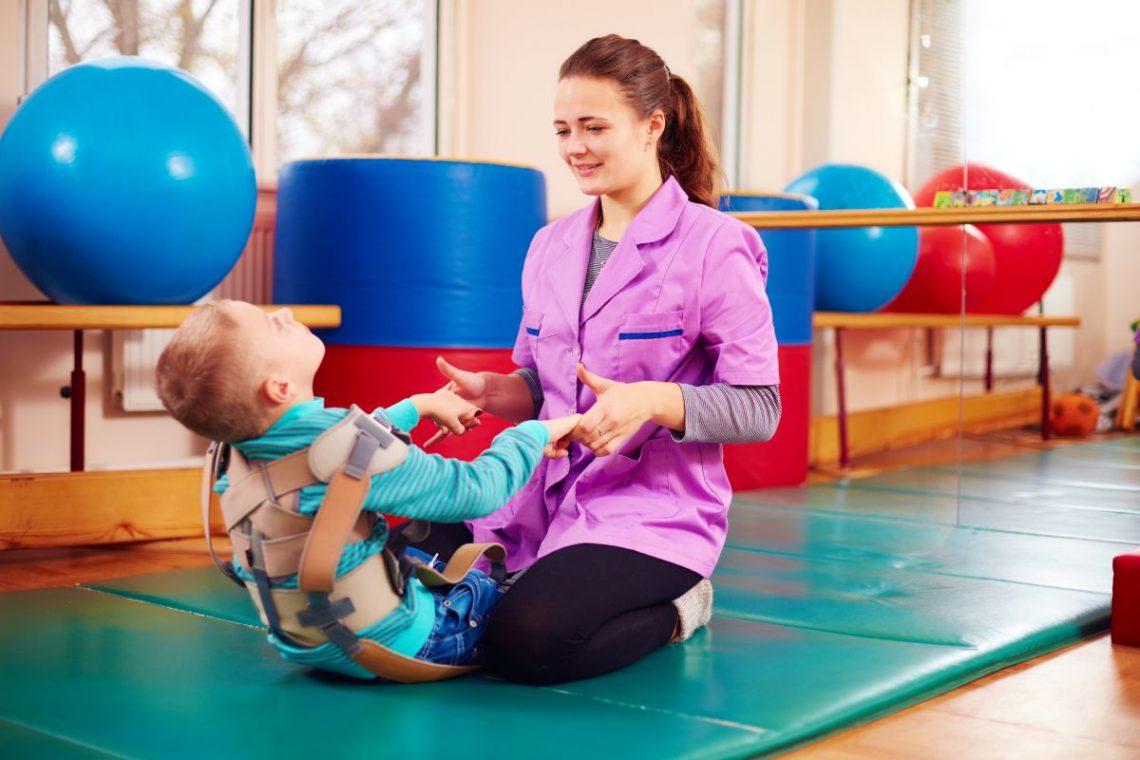 rehabilitantka ćwiczy na macie z małym chłopcem