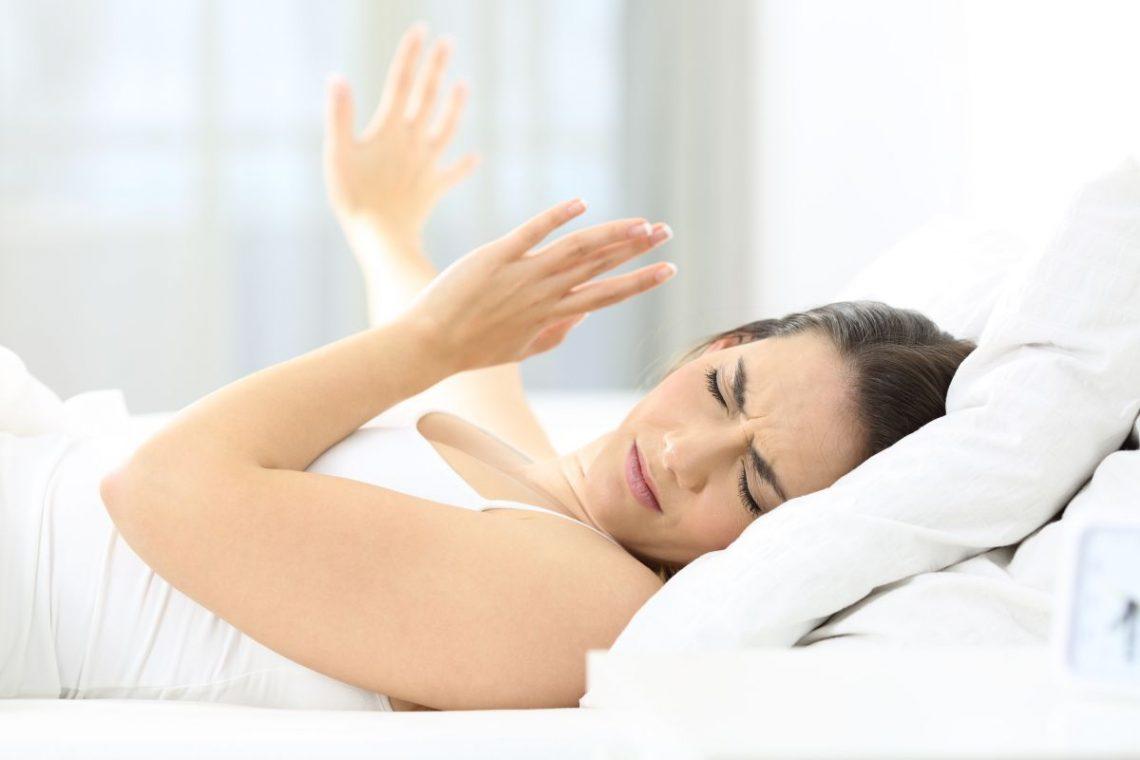 kobieta leżąca w łóżku zasłania się przed słońcem padającym z okna