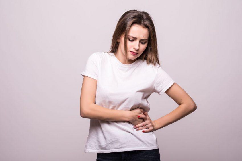 Kobieta w białej bluzce trzyma się za lewą stronę brzucha