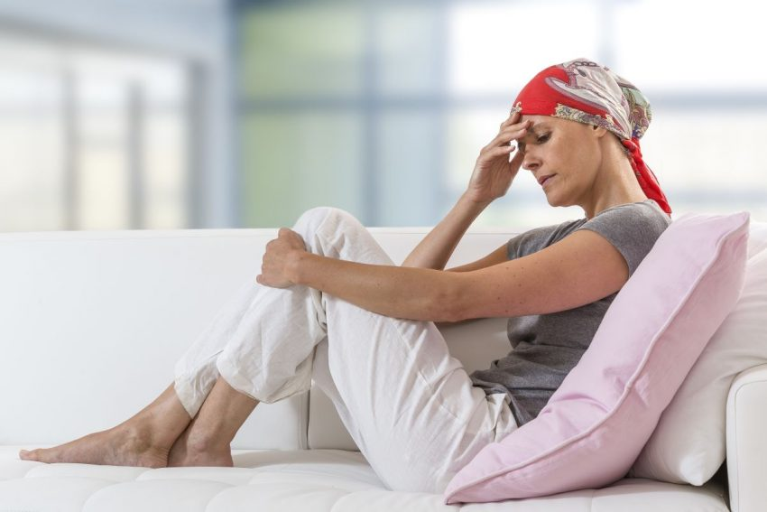 kobieta z chustką na głowie siedzi na kanapie ze spuszczoną głową