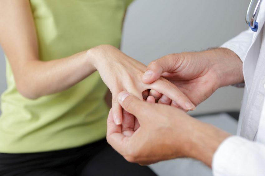Kobieta w zielonej bluzce pokazuje lekarzowi swoje dłonie