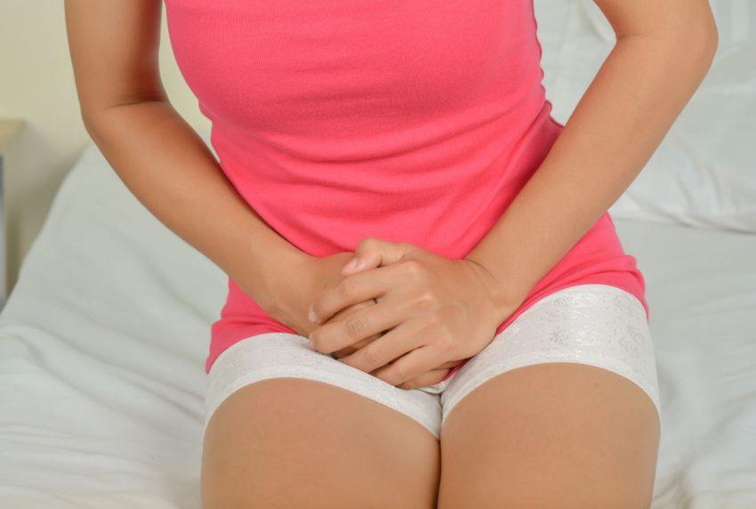 młoda kobieta siedząca na łóżku trzyma się w miejscu intymnym