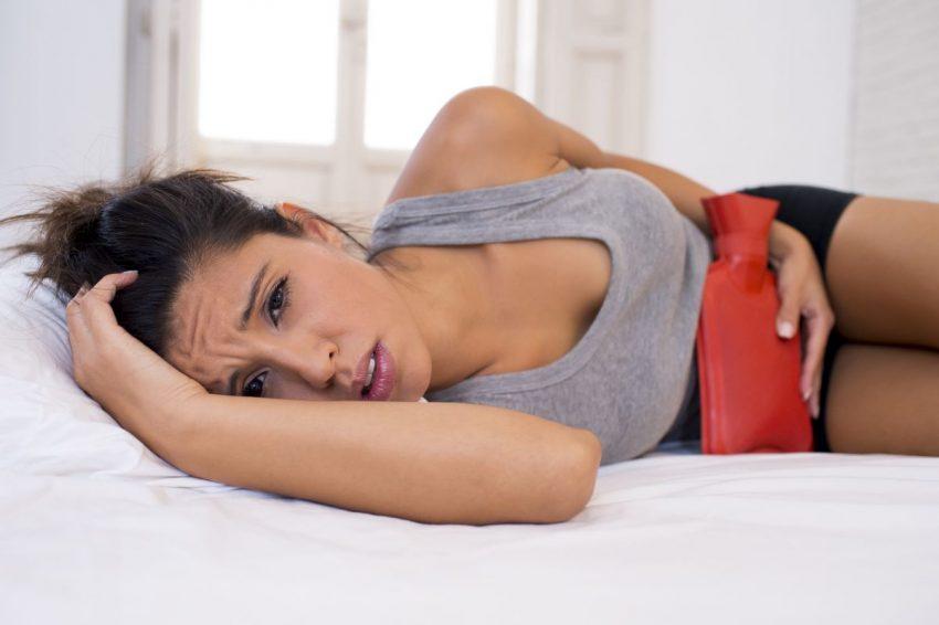 Kobieta w szarej bluzce leży na łóżku z termoforem