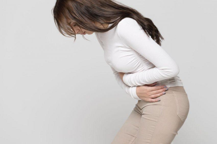 młoda kobieta stoi i trzyma się za brzuch