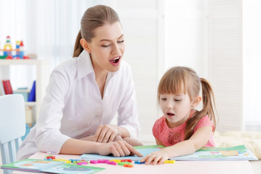 kobieta i dziewczynka siedzą przy stoliku i ćwiczą mowę