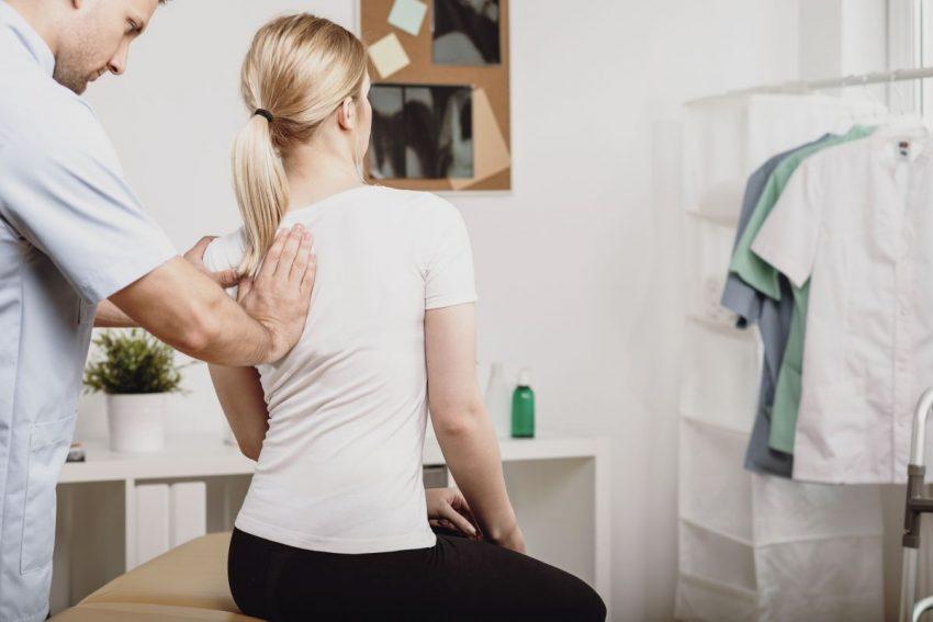 Lekarz bada kręgosłup pacjentki odwróconej tyłem