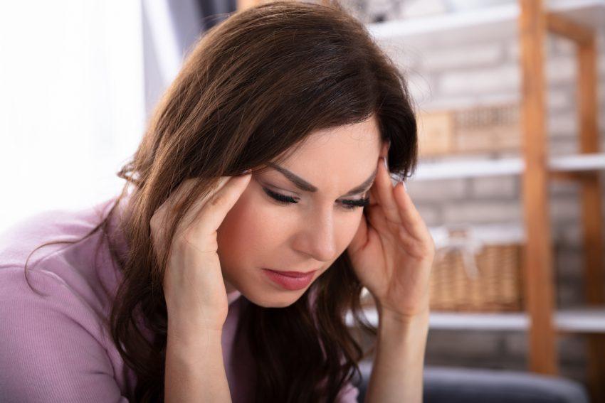 Kobieta odczuwająca szum w głowie trzyma się za skronie.