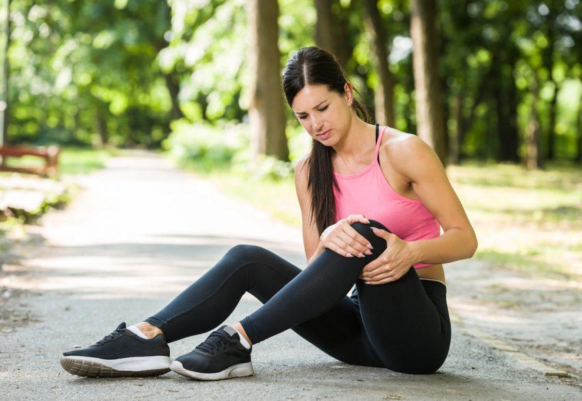 Torbiel Bakera - Młoda kobieta siedzi na ścieżce w parku i trzyma się za bolące kolano.