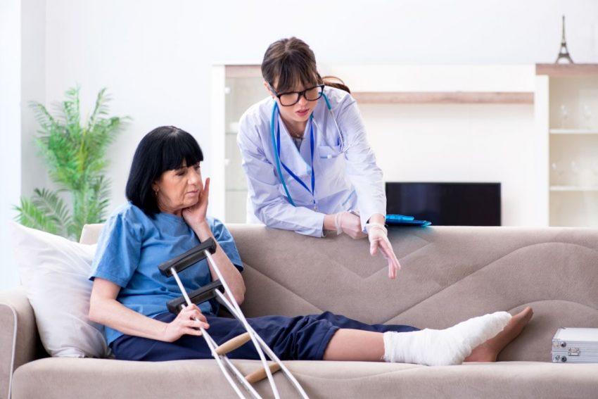lekarka rozmawia z kobieta siedząca na łożku z nogą w gipsie i kulami