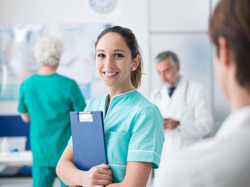 Lekarka stoi z teczką i się uśmiecha