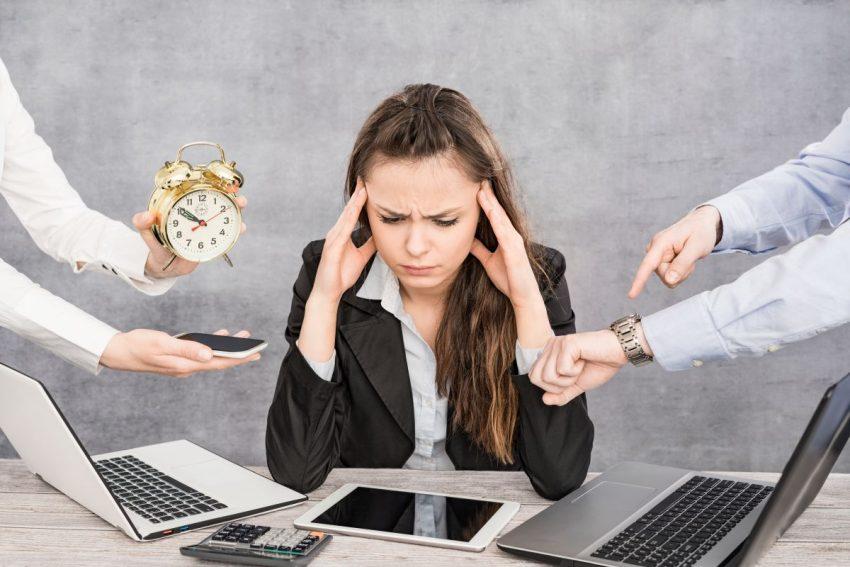 młoda kobieta przy biurku ze smutną miną z dwoma laptopami, zegarkiem, telefonem, tabletem