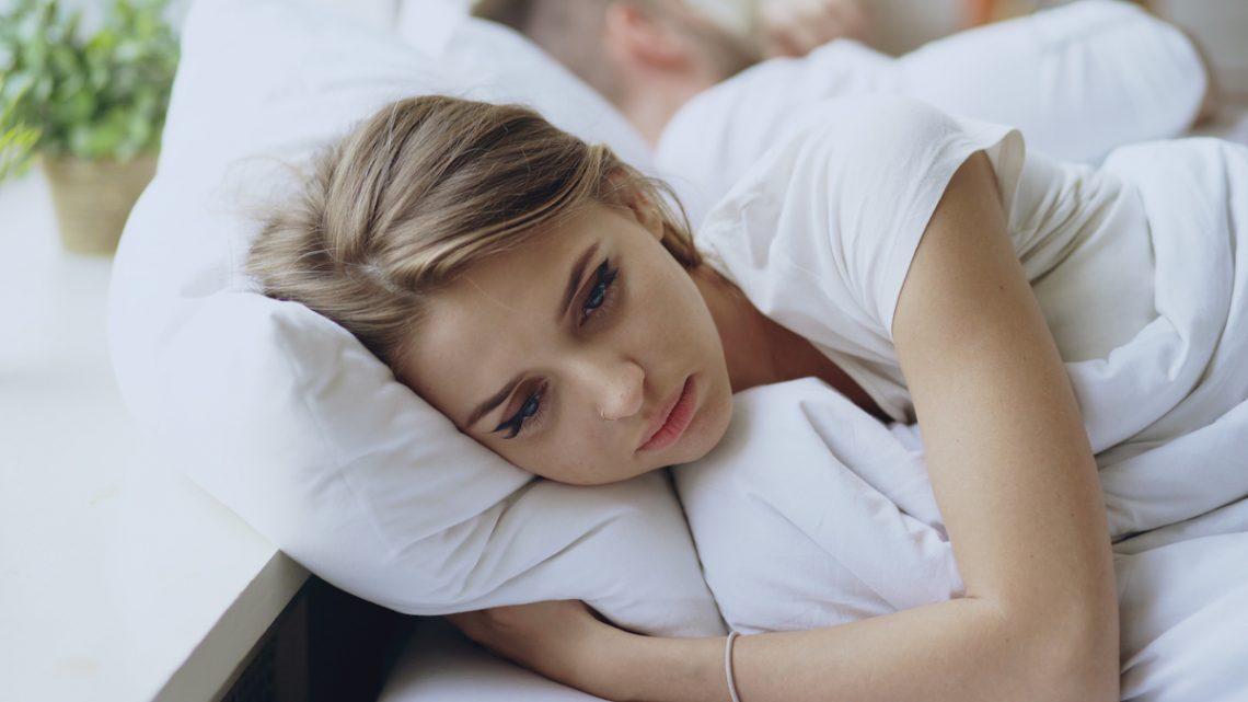 Młoda kobieta cierpiąca na zaburzenia hormonalne leży przygnębiona w łóżku.