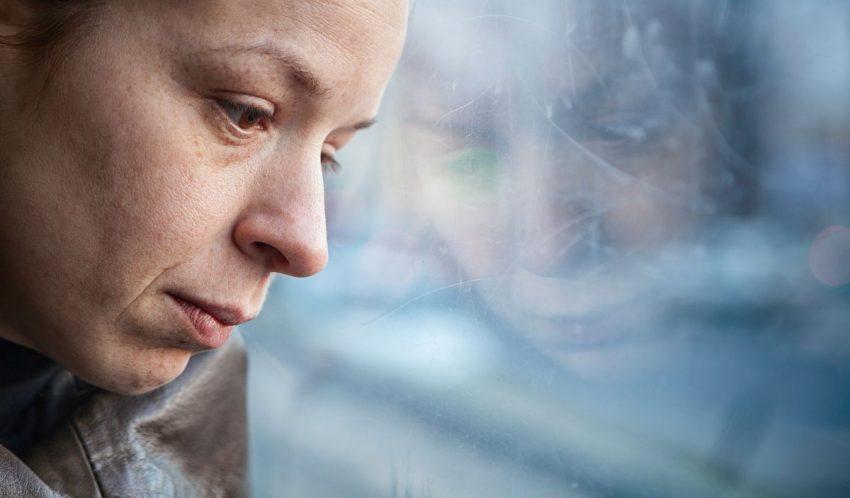 Kobieta stoi smutna przy szybie i patrzy przed siebie