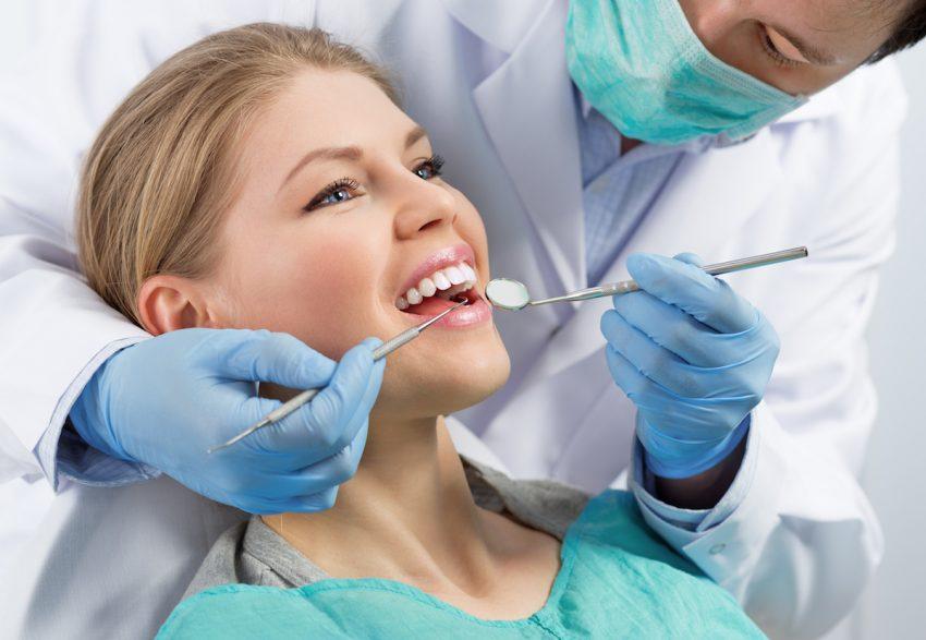 Kobieta cierpiąca na zapalenie dziąseł podczas wizyty u dentysty.