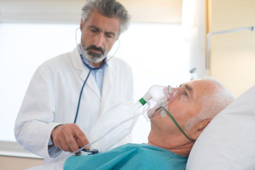 Lekarz bada pacjenta, który leży w masce tlenowej