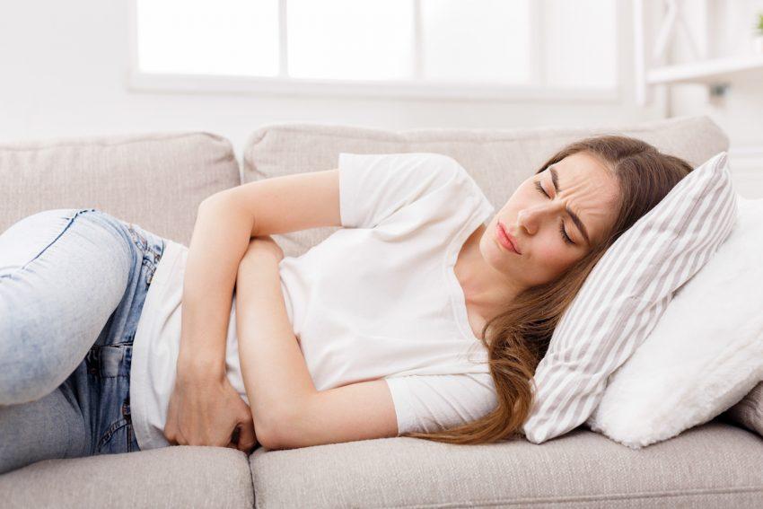 Kobieta z zapaleniem otrzewnej leży skulona i trzyma się za obolały brzuch.
