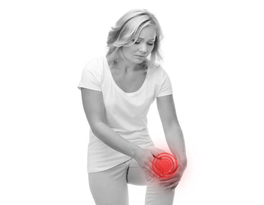 kobieta stojąc trzyma się za jedno kolano