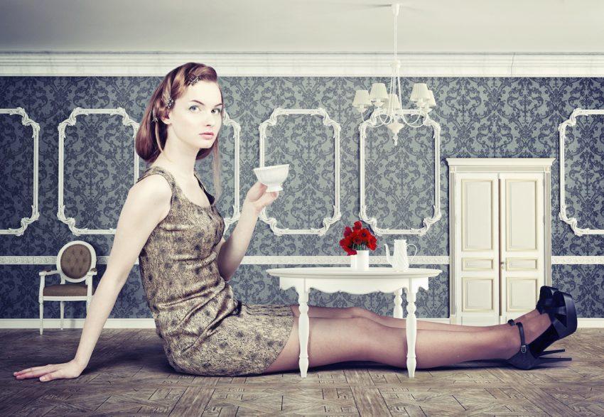 Kobieta cierpiąca na akromegalię siedzi przy stole z filiżanką w ręku.