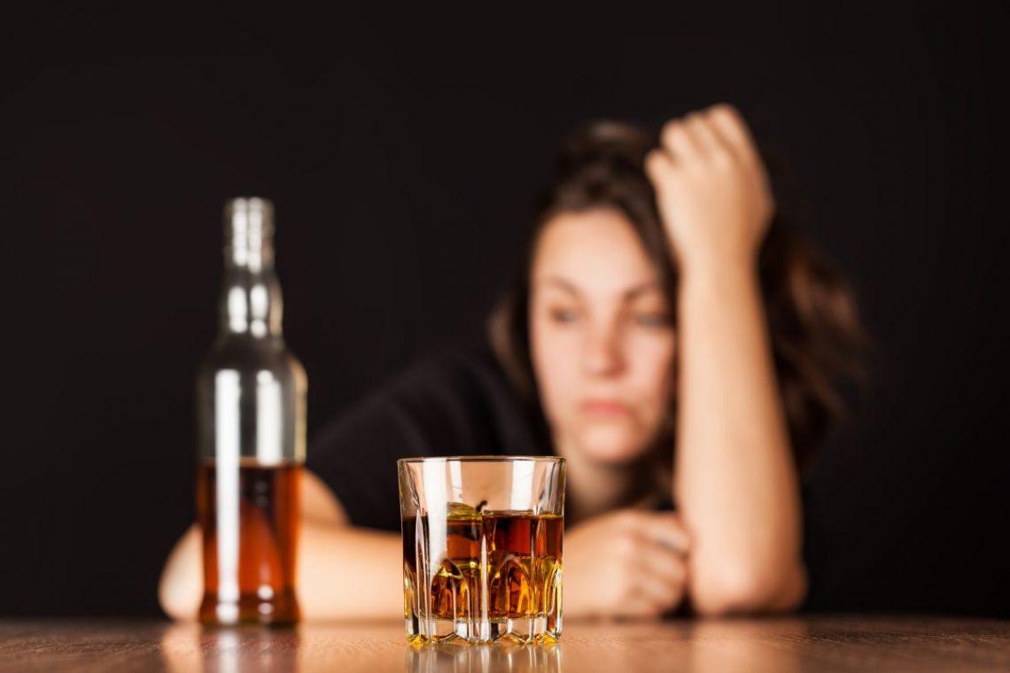 kobieta siedzi zmartwiona za butelką alkoholu