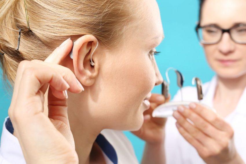 Kobieta w blond włosach przymierza aparat słuchowy