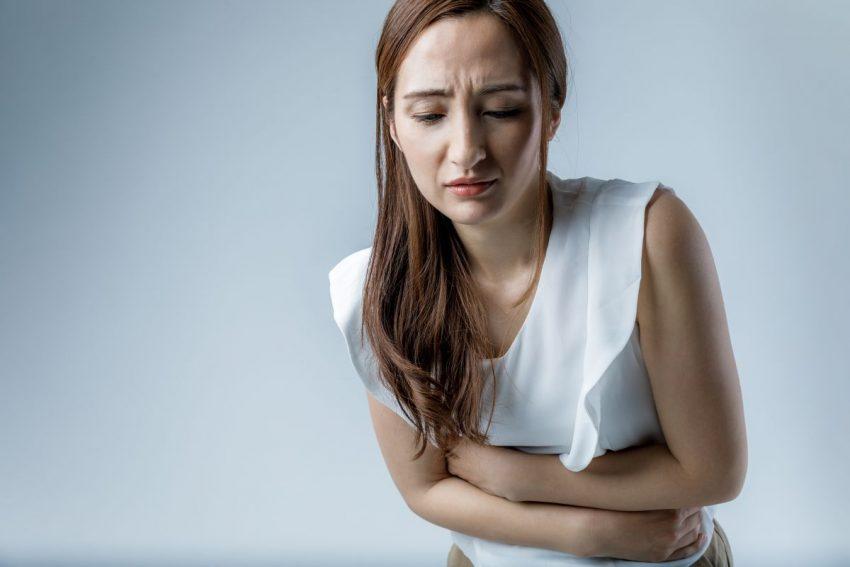 Kobieta w białej bluzce trzyma się z bólu za brzuch