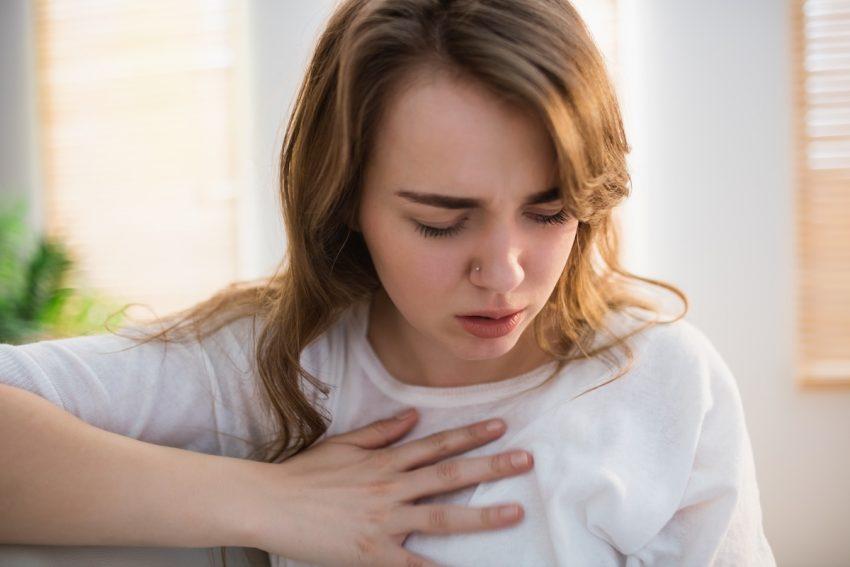 Kobieta cierpiąca na częstoskurcz nadkomorowy trzyma się za klatkę piersiową.