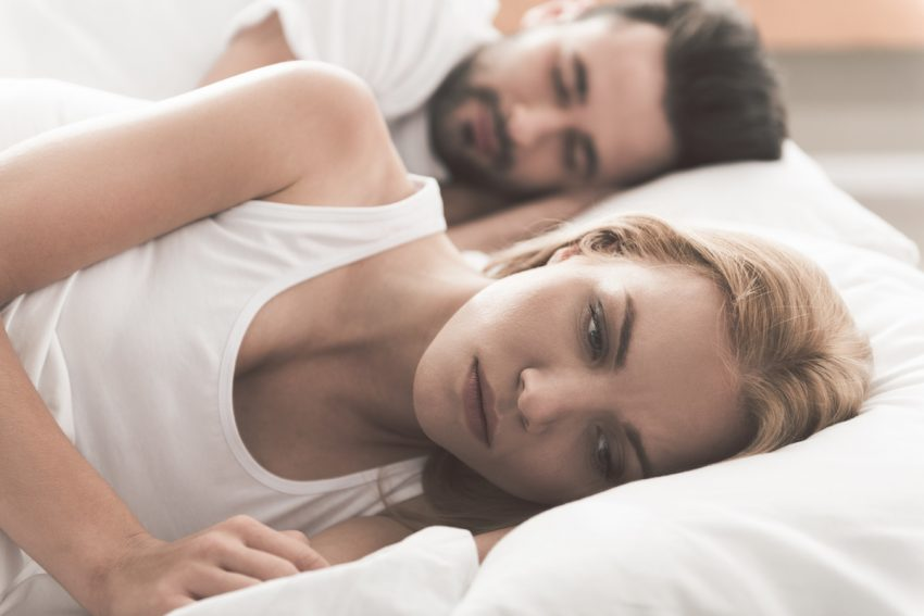 Kobieta z dyspareunią leży przygnębiona w łóżku obok swojego partnera.