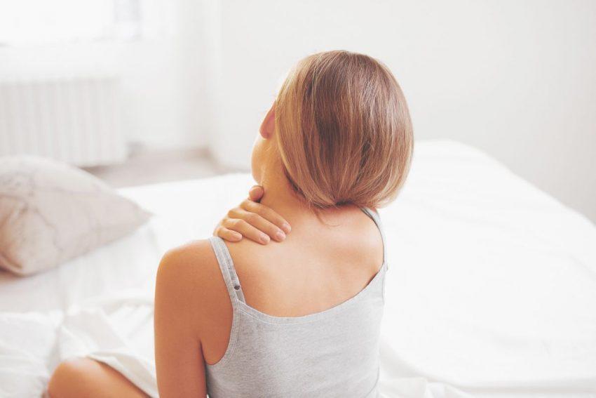 Kobieta siedzi na łóżku i trzyma się za kark
