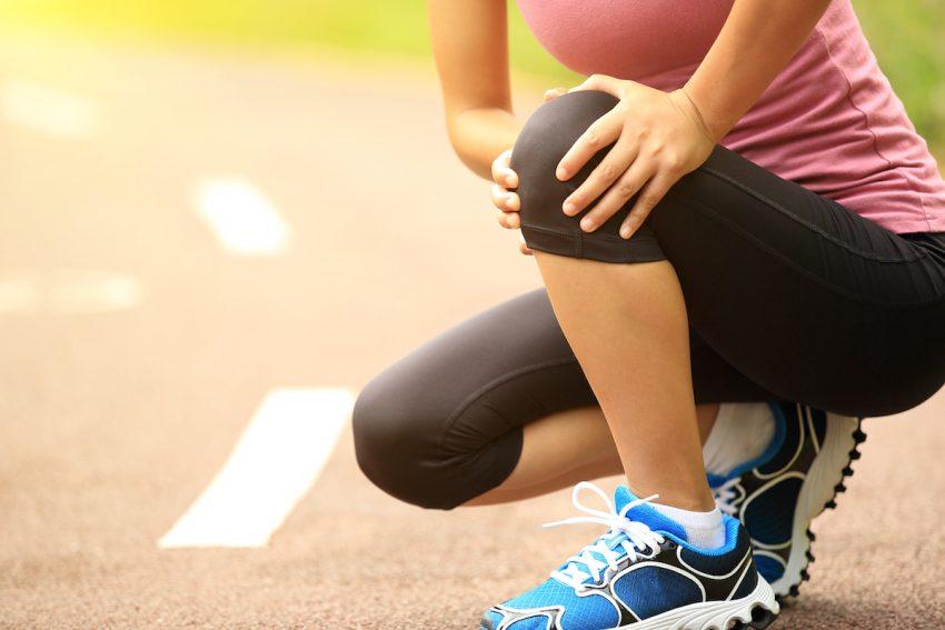Kobieta z dystorsją trzyma się za bolące kolano.