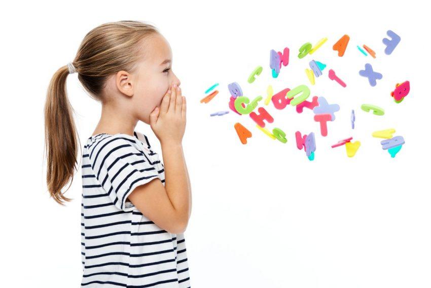 Dzieckok trzyma się za policzki, a z jego ust wychodza kolorowe literki