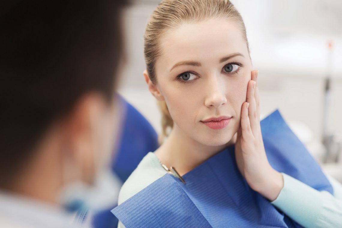 Kobieta z bólem zęba rozmawia z dentystą przed zabiegiem ekstrakcji zęba.