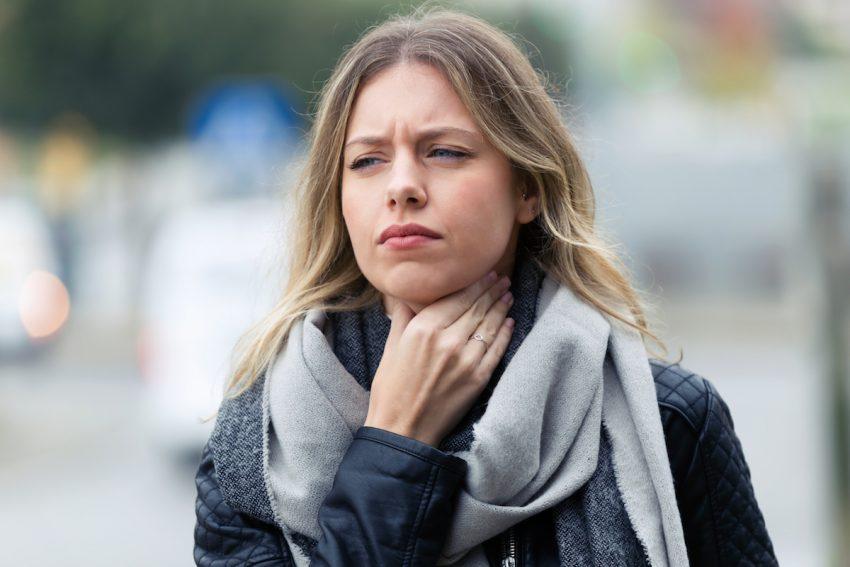 Kobieta dotyka gardła, ponieważ czuje zalegającą w nim flegmę.