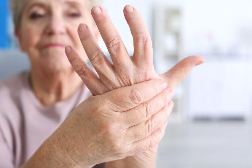 Starsza kobieta trzyma się za dłonie
