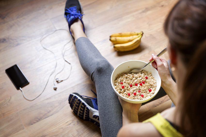 Kobieta siedzi na podłodze i je