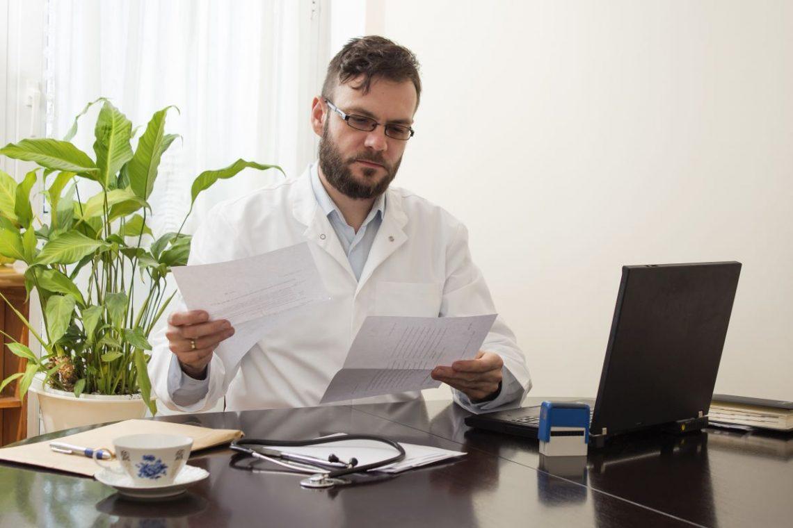 Lekarz siedzi za biurkiem i przegląda wyniki badań pacjenta