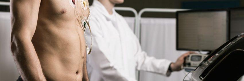 Mężczyzna jest badany przez kardiologa za pomoca aparatury