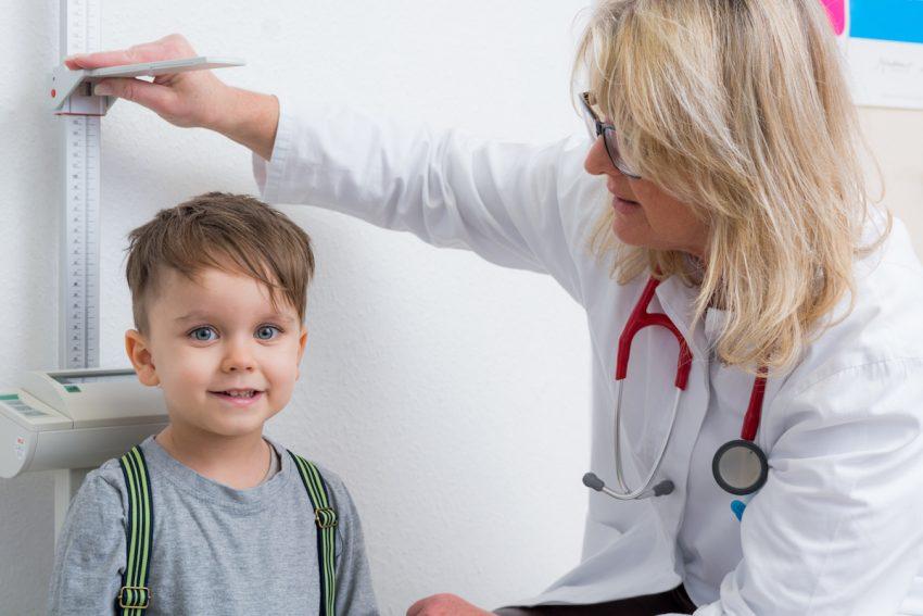Karłowatość - Lekarka mierząca wzrost małego chłopca.