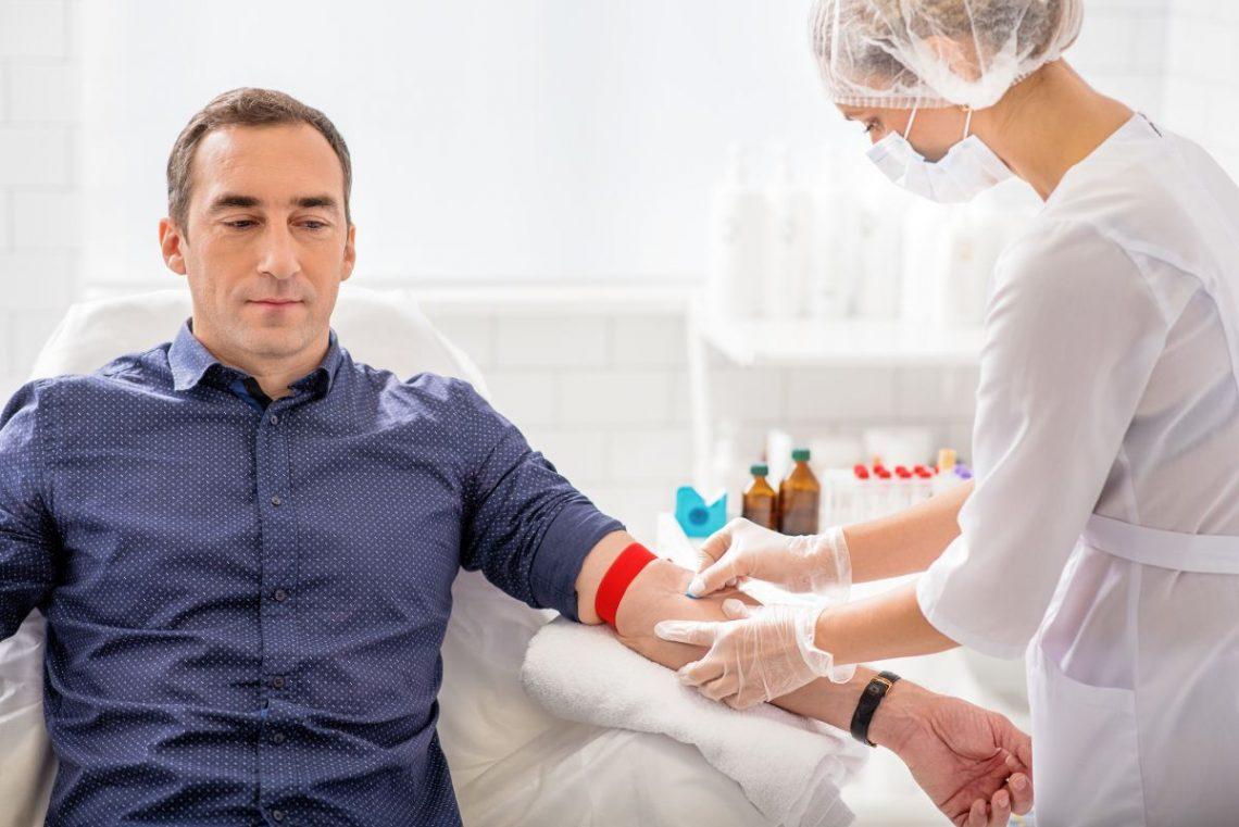 Mężczyzna siedzi na fotelu w punkcie pobrań i ma pobieraną krew