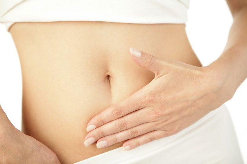 Kobieta w bieliźnie trzyma się za brzuch w okolicach żołądka