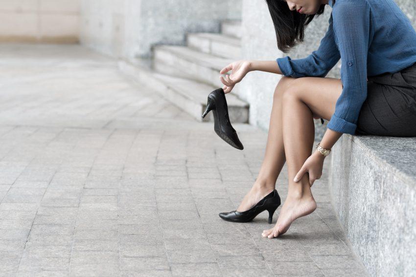 Kobieta z nerwiakiem Mortona masuje nogę.