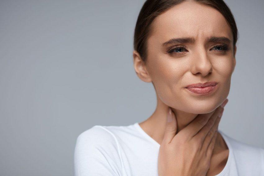 młoda kobieta z grymasem bólu na twarzy trzymająca się za gardło