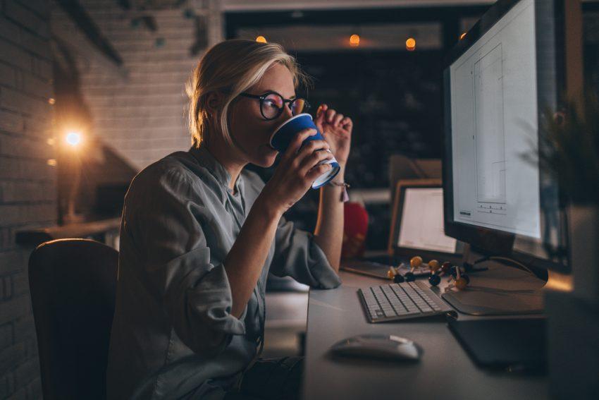 Kobieta pije kawę przed monitorem