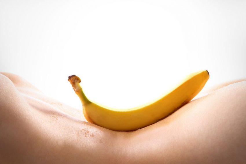 Na ciele kobiety leży banan
