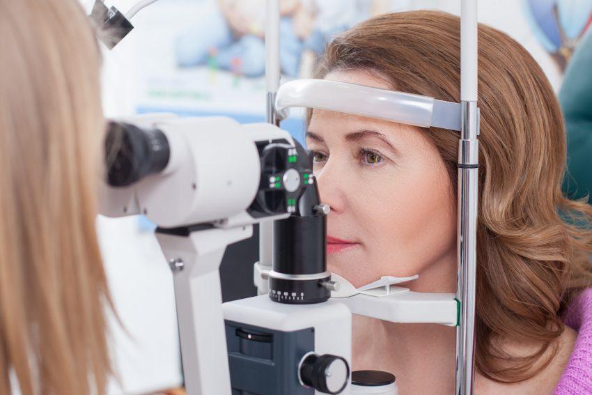 Kobieta z przekrwionymi oczami podczas badania okulistycznego.