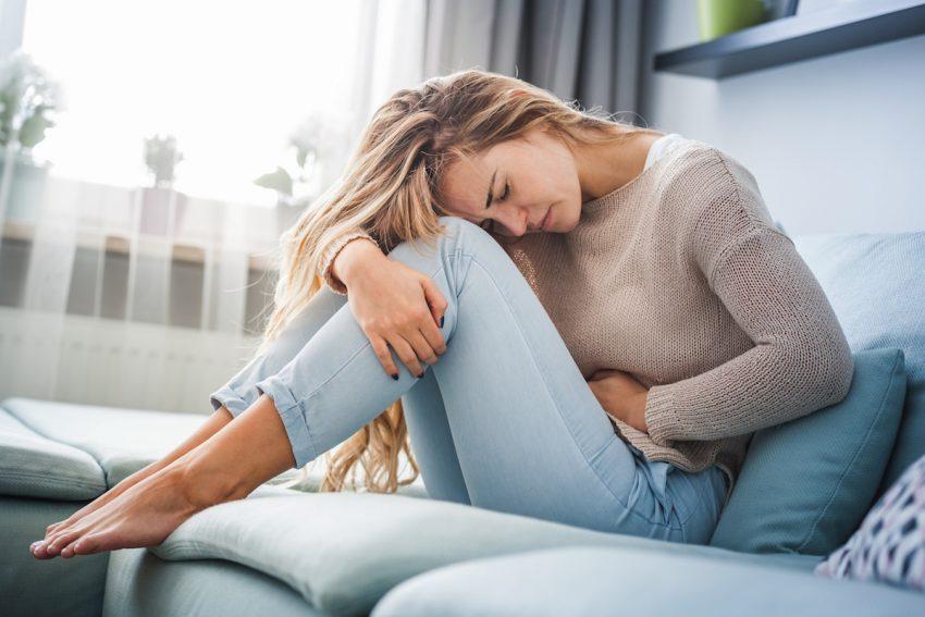 Kobieta cierpiąca z powodu bólu i przelewania w brzuchu siedzi skulona na kanapie.