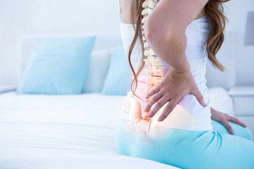kobieta siedząca na łóżku trzymająca się za lędźwie