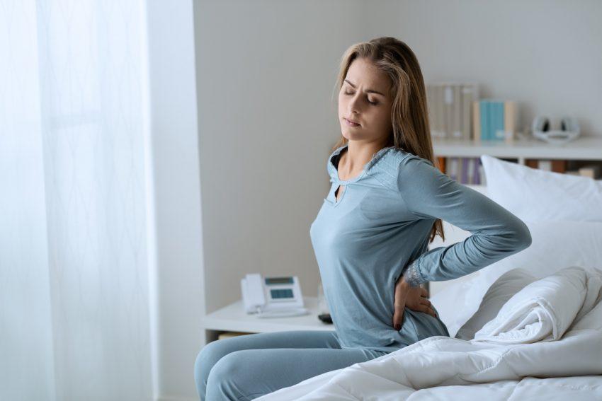Kobieta cierpiąca na raka narki trzyma się za obolałe miejsca.