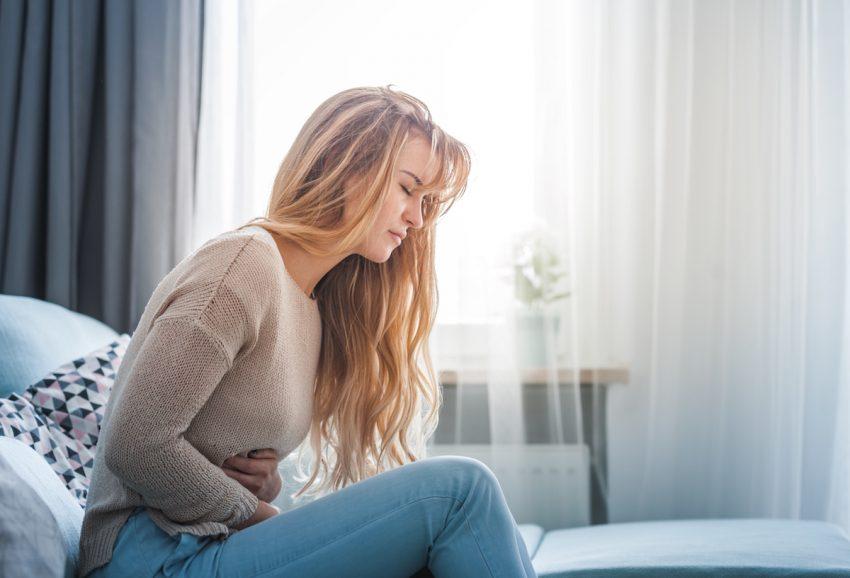Kobieta z rakiem macicy trzyma się za bolący brzuch.