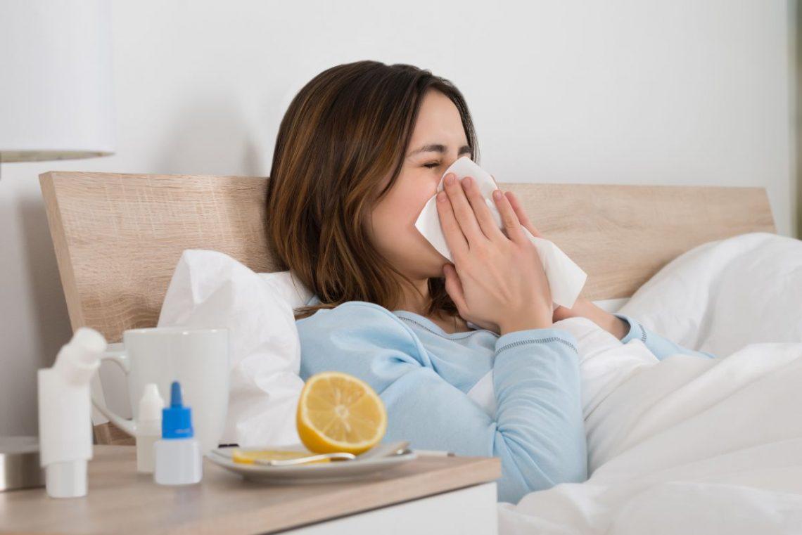Kobieta leży chora w łóżku z chusteczkami, obok niej stoją lekarstwa